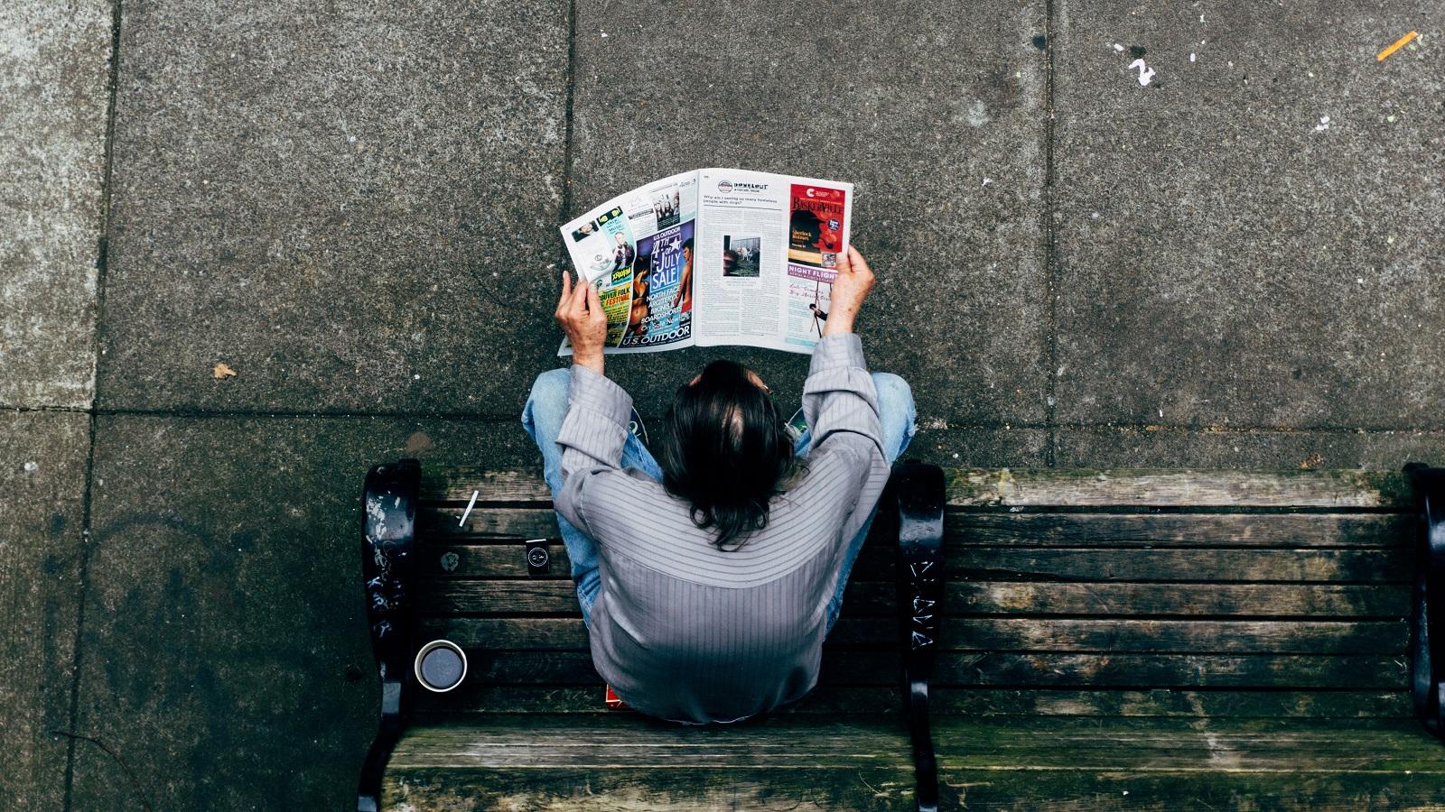 Ein Mann auf der Bank mit einem Magazin oder einer Zeitung. (Foto: Mike-Ackerman, Unsplash.com)