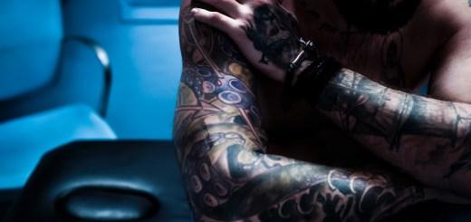 Ein nachdenlicher Mann mit Tatoos. Er ist allein. Yuriko Yushimata schreibt über Angst und Nähe. (Foto: Celine Preher, Unsplash.com)