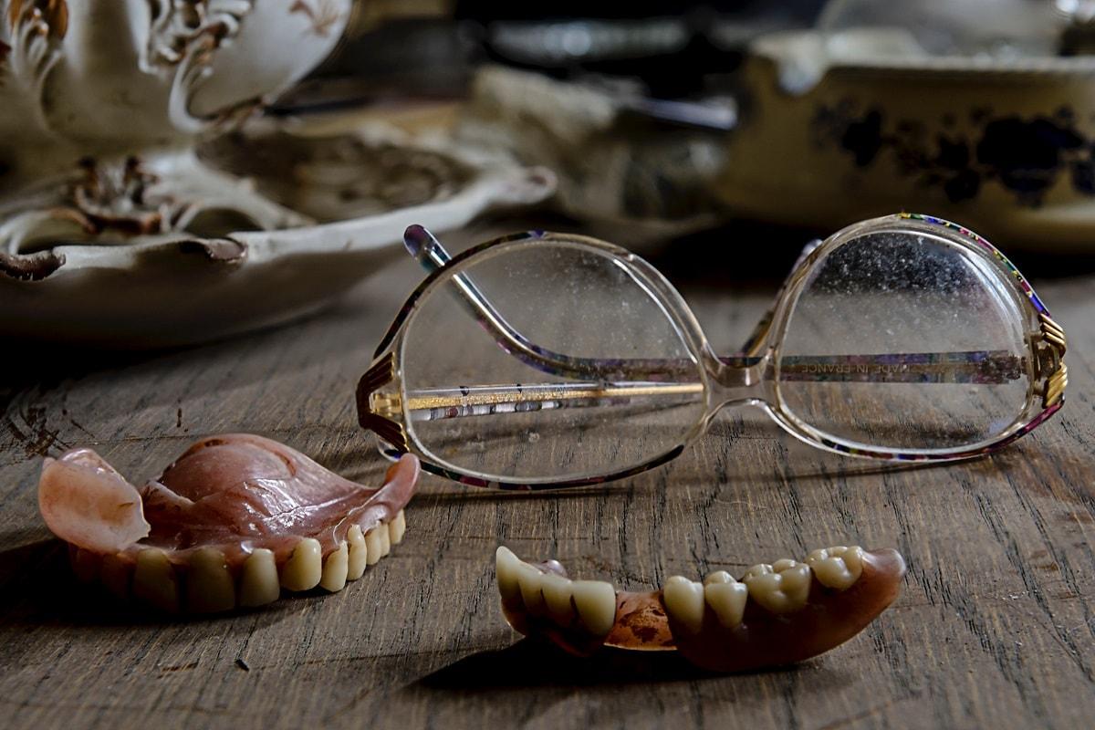 Kaputte dritte Zähne und eine verschmutzte Brille auf einem Tisch. (Foto: Paul Morris, Unsplash.com)