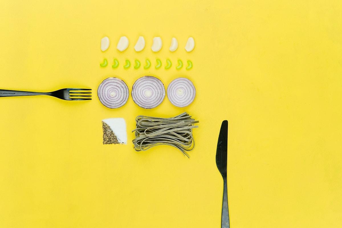 Messer, Gabel und Gemüse auf gelben Untergrund. (Foto: Toa Heftiba, Unsplash.com)