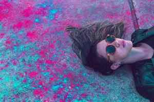 Himmel oder Hölle? Eine Frau liegt auf einem mit roter und türkisfarbiger Flüssigkeit bespritzten Gehsteig. (Foto: Lucas Lenzi, Unsplash.com)