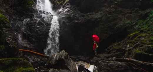 Ist ein Green New Deal der Ausweg? Eine Frau mit Regenschirm an einem Wasserfall. (Foto: Caleb Ralston, Unsplash.com)