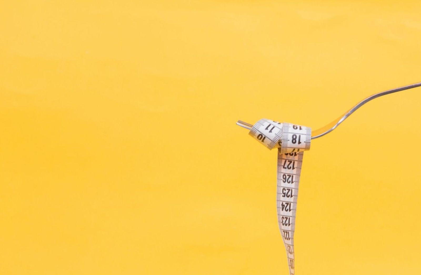 Gabel und Massband vor gelben Hintergrund als Symbol für den Versuch der Gewichtsreduktion. (Foto: Diana Polekhina, Unsplash.com)
