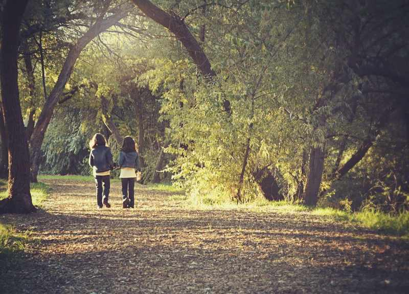 2 girls walking down a forest path