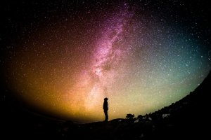 A person silhouetted against a galaxy