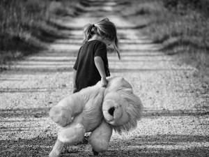 Grayscale image of a girl holding a teddy bear walking down a path with her head down