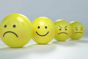 4 Emoji balls. First is sad, second is happy, third is angry, fourth is worried. The second one is in focus, the rest are blurred.
