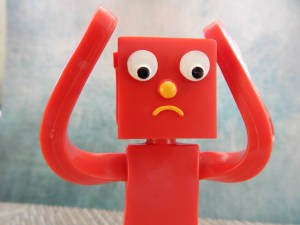 Sad gumby blockhead with its arms raised to its head