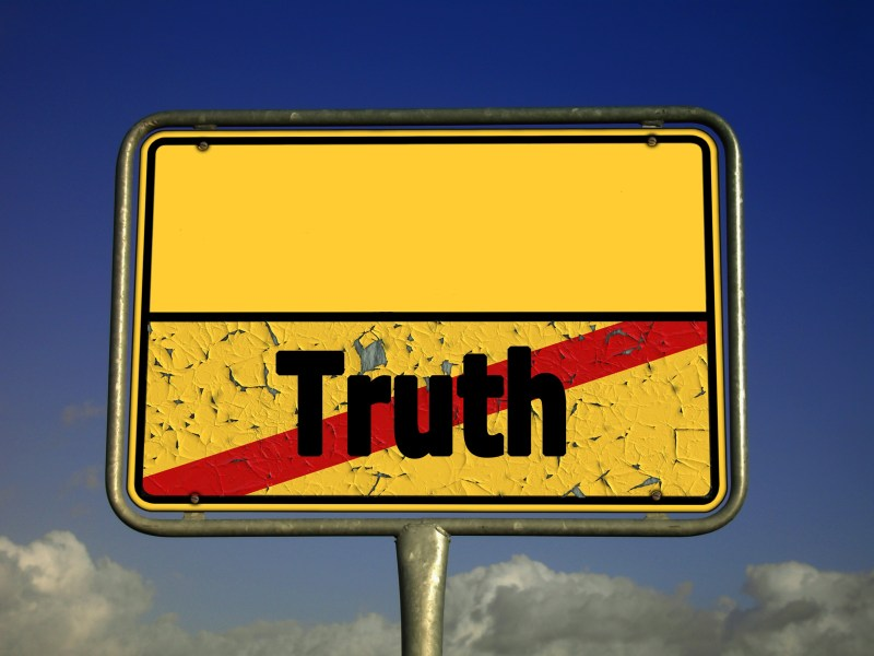 """A yellow sign board. The upper half is blank while the lower half has """"Truth"""" written which is crossed out."""