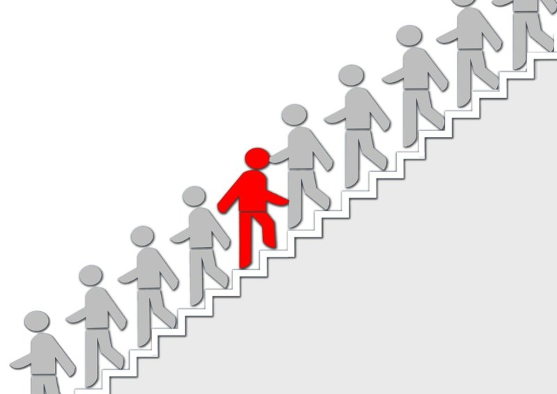 Gray stick figures walking downstairs. One red one climbs upstairs