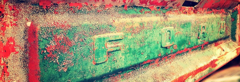"""An antique, rusted nameplate reading """"FORD"""""""