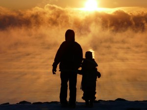 An adult and a child silhouetted against the sun