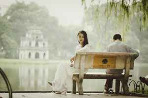 A man and woman sitting on a bench. The woman looks to the side, one leg crossed over the other with her back to the man. The man is looking down presumably reading something.