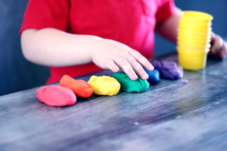 young child lining up playdough in the colors of the rainbow from red to violet.