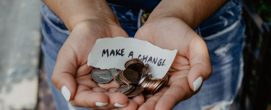 "A woman holds a handful of coins and a slip of paper with a hand-written note which reads ""make a change"""