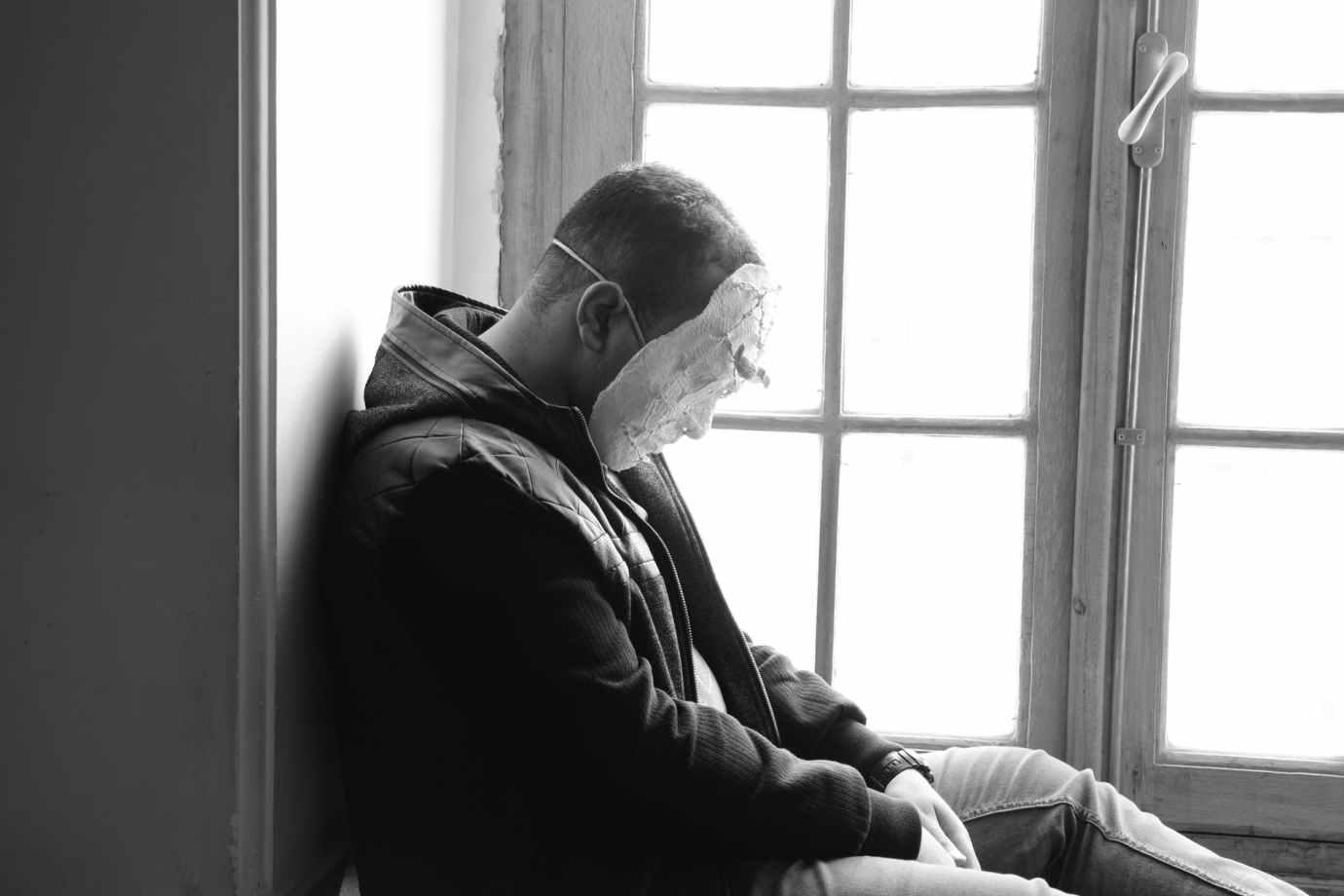 man wearing mask sitting near window panel