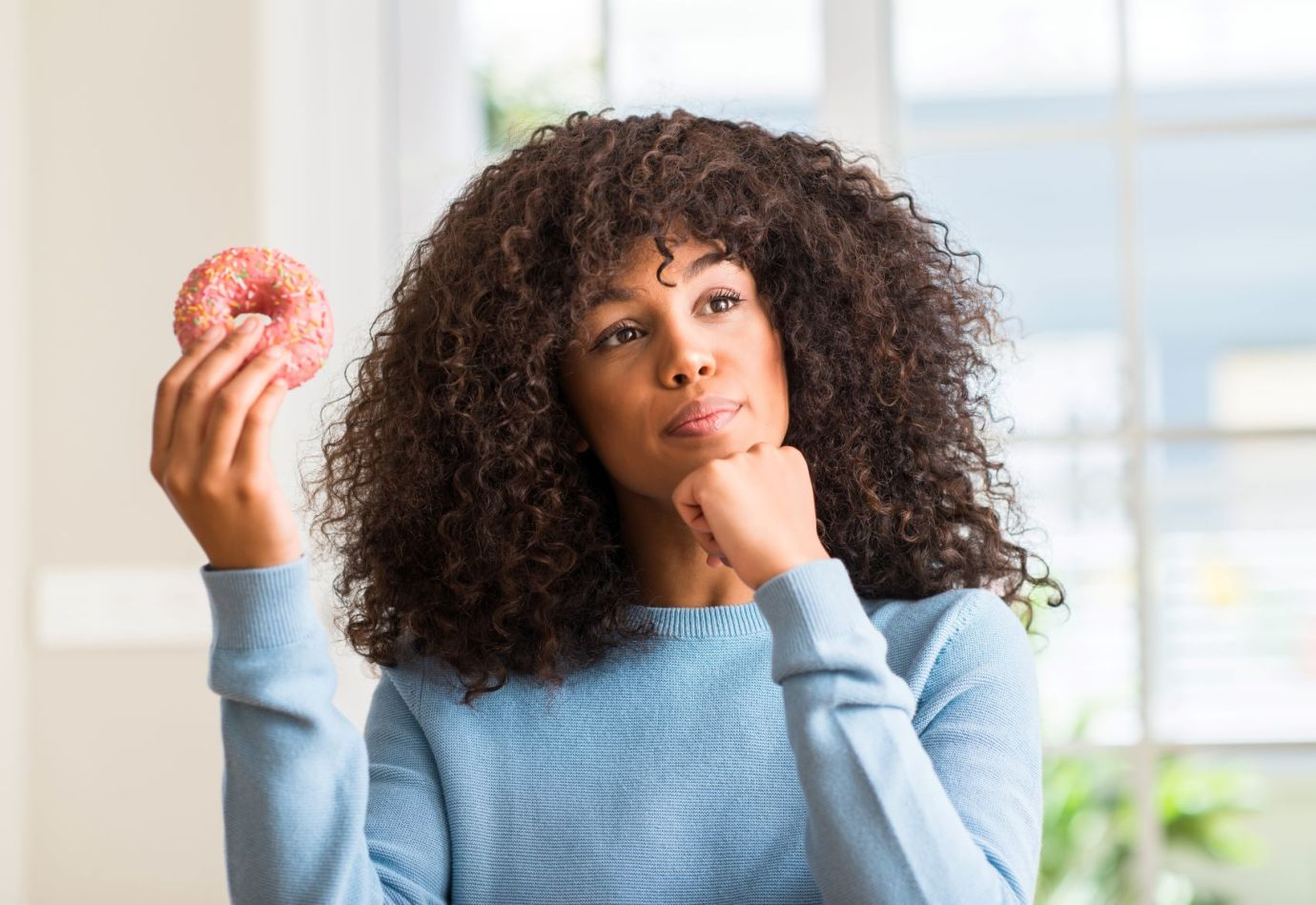 Black woman in a thinking pose, confused, sitting down while holding a pink donut with sprinkles in a blue sweater.