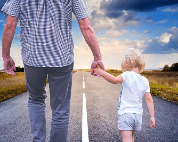 4-year-old child holding a father's hand and walking on a road with a field on either side and an open blue sky with white clouds.