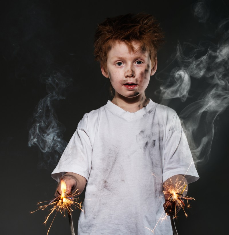 white redhead boy holding sparkler in his hands which had just exploded.