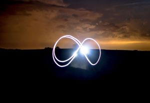 A bright infinity symbol in the evening orange sunset on a field.