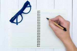 Someone writing in a notebook with a pair of blue glasses folded up on the notebook.