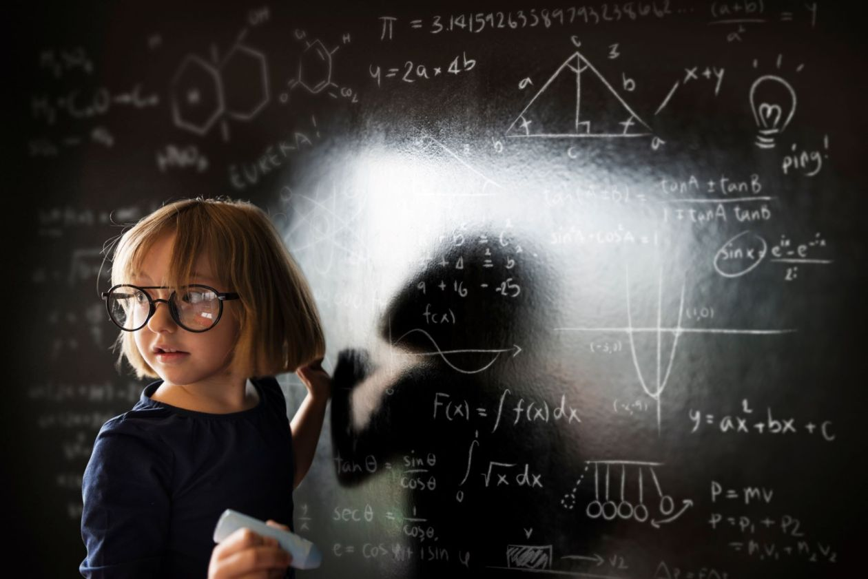 White girl wearing glasses writing calculus equations on a chalkboard, looking away from the camera and the chalkboard.