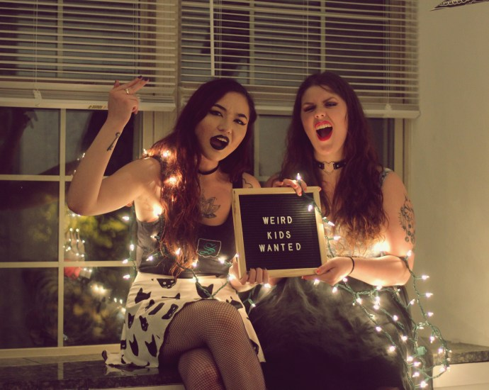 "Two women holding a sign that says ""Weird kids wanted"" with white lights around their arms."