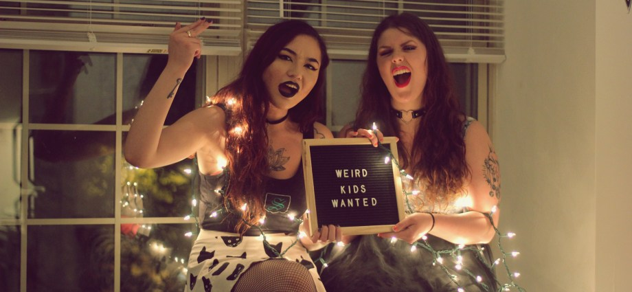 """Two women holding a sign that says """"Weird kids wanted"""" with white lights around their arms."""