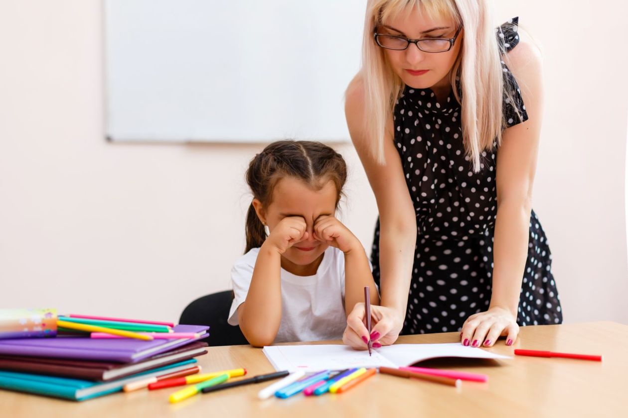 A child rubbing her eyes  and a woman writing in the child's notebook next to her.