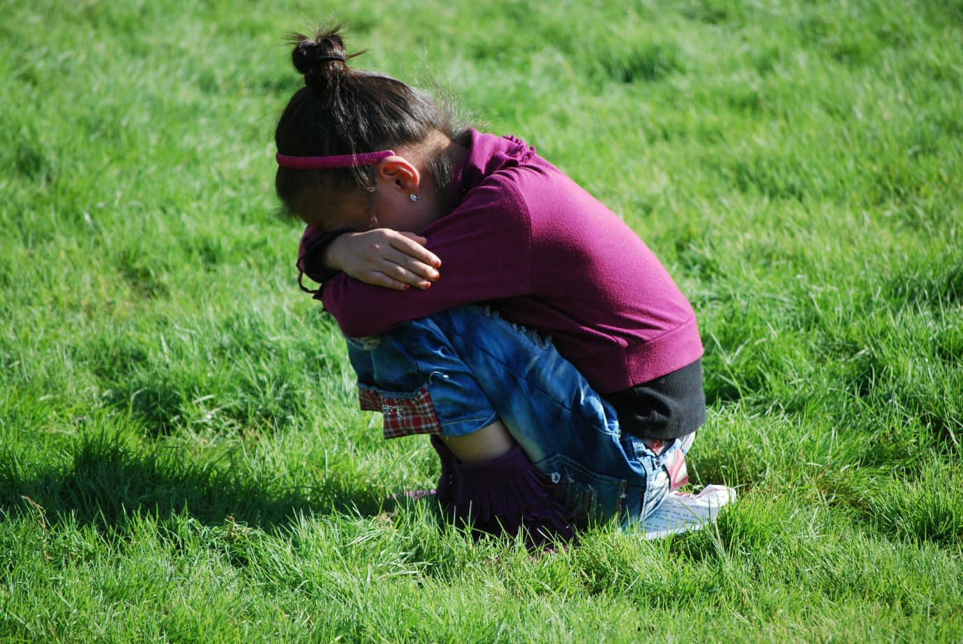 Girl crying crouching in a field with her head on her arms.