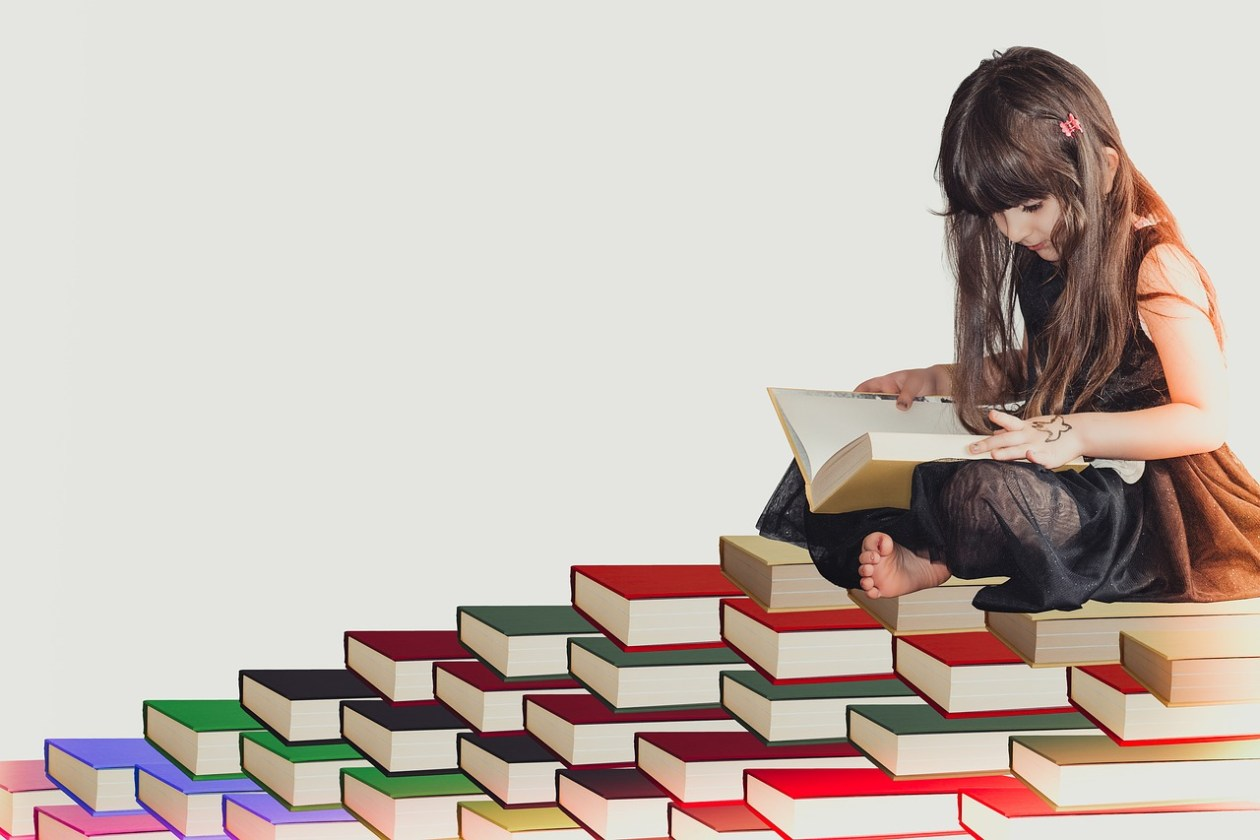 Girl photoshopped sitting on a bunch of pile of books while also reading a book.