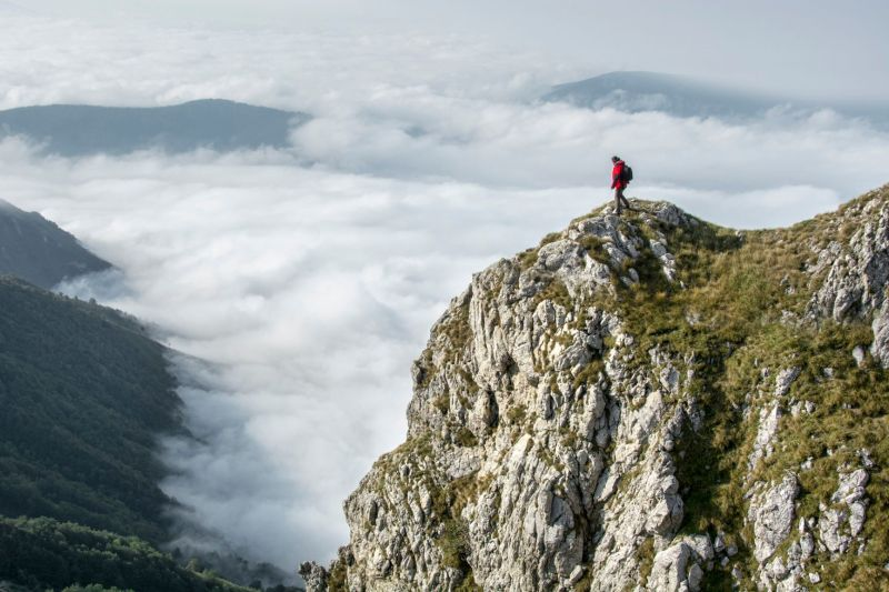 Photograph of person on a mossy mountain by themselves in a red jacket and backpack with clouds in the background. below the mountain.