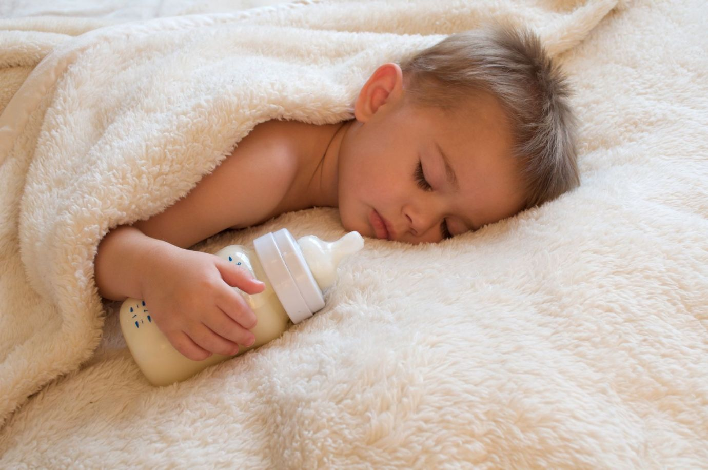 Young child sleeping in a soft blanket holding a bottle of milk.