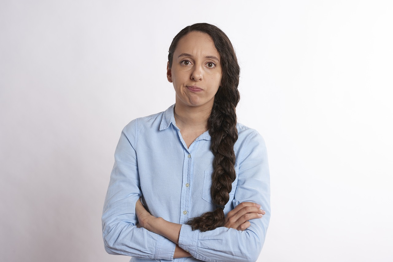 Woman looking unenthused with arms crossed into the camera.