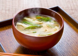 steaming miso soup in a dark red bowl