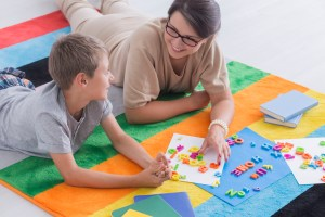 Adult woman laying on colorful rainbow rug with boy solving word problems with coloful magnet letters.