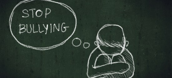 "Chalk drawing of a child huddled up with a thought bubble that reads ""stop bullying"""