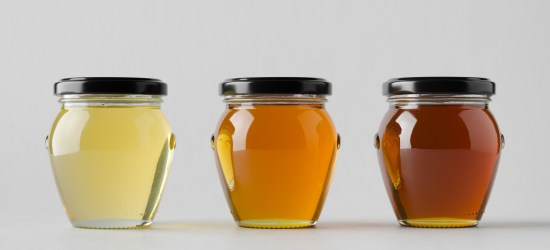 Three clear honey jars of different shades from light to dark.