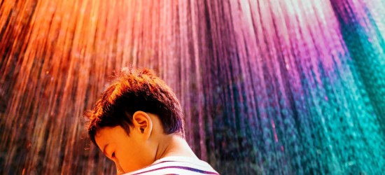 A young boy with autism faces an abstract wall of rainbow colors