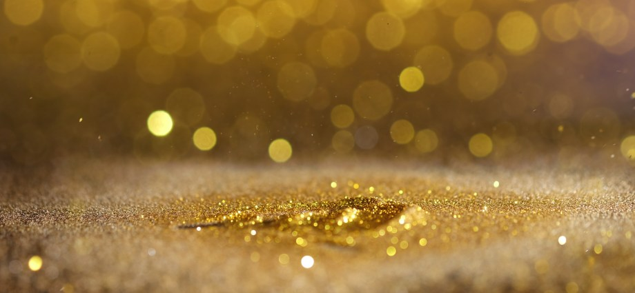 image has a lovely pile of gold glitter with glitter raining down and sparkling in the background to celebrate our golden moment for autistic coming out day