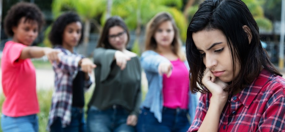 A group of girls, standing outside, bullying a young adult woman by calling her out.