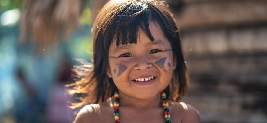 indigenous girl child about three or four years old with face paint and a beaded necklace, smiling.
