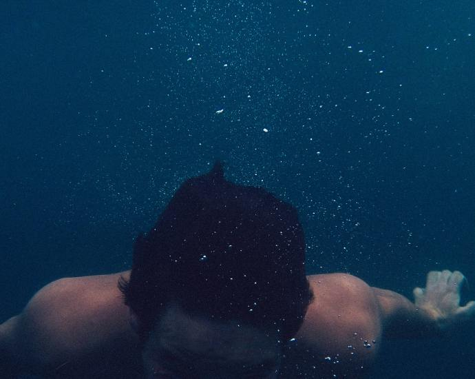 Man under water, bubbles rising to surface