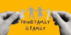 found family is family text with a pair of hands holding a paper cut out of a family
