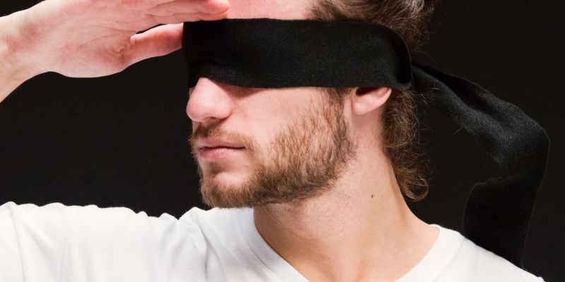 man with a square jaw line and beard wearing a blindfold.