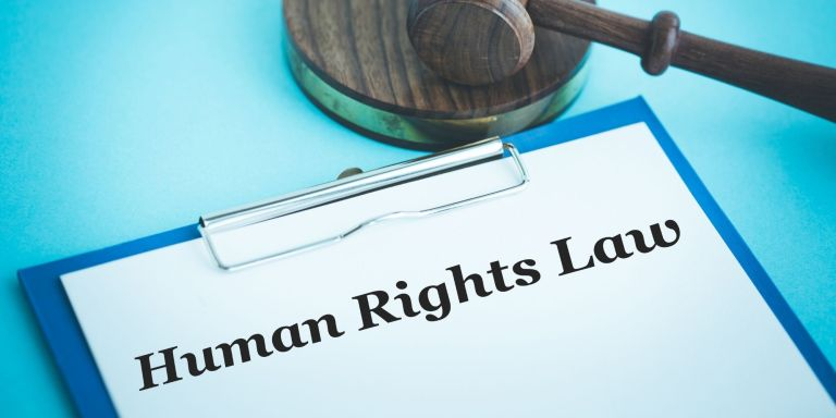 Human rights law on a clipboard with a gavel in the background