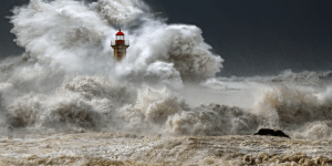 Image of a lighthouse in a storm about to be covered by a wave. Image is a metaphor for how an autistic person with autism may feel during a meltdown
