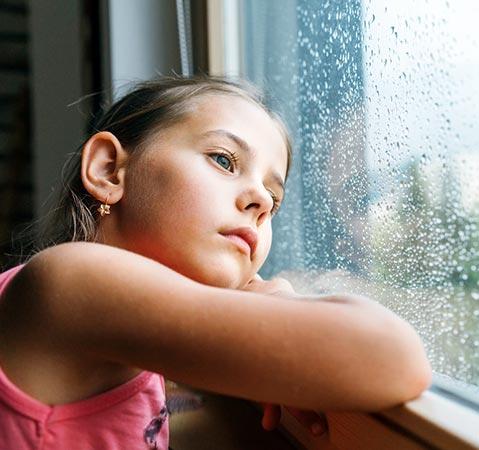 Menina aborrecida na janela