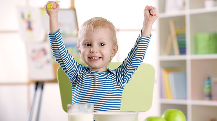 Happy toddler eating breakfast with hands up