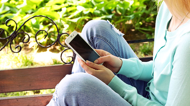 Young woman using smartphone outdoors